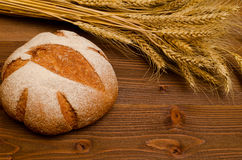 Round rye bread and ears of wheat on a wooden table. Top view Stock Photos