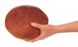 Round rye bread in female hand  on white background. Round rye bread in a female hand  on white background Royalty Free Stock Photography