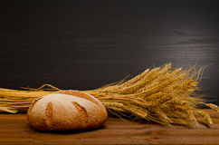 Round rye bread and a sheaf on wooden table, black background. Space for text Royalty Free Stock Photo