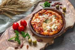 Round sausage pizza Margherita on a beautiful natural blackboard of olive . Selective focus. Royalty Free Stock Photos