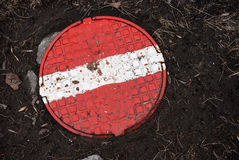 Round sewer manhole with red stop sign Stock Image