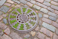 Round sewer manhole on stone pavement Royalty Free Stock Image