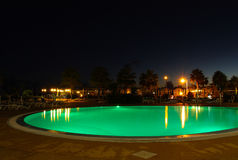 Illuminated green pool at night. Round shape hotel outdoors swimming pool at night illuminated in green with reflections on a calm water Royalty Free Stock Image