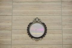 Round shape mirror with beautiful frame. On the wall, clouse view royalty free stock photography