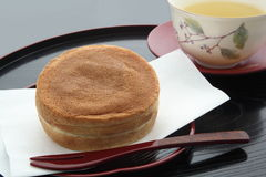 Round-shaped Cake Containing Red Bean Paste, Japanese Sweets. Japanese muffin containing bean jam, served hot and hot green tea Royalty Free Stock Photography
