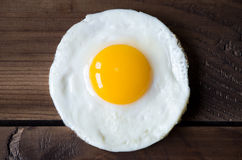 Round shaped fried egg for healthy breakfast on dark wooden backgrond Stock Photos