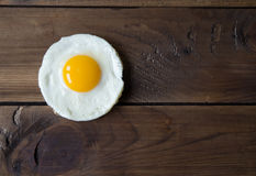 Round shaped fried egg for healthy breakfast on dark wooden backgrond Royalty Free Stock Photo