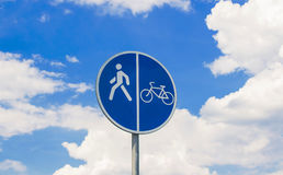 Round sign road for bicycles and pedestrians. Round, blue sign of a walkway for bicycles and pedestrians on a cloudy background Stock Image