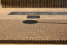 Round sign shadow on pavement. Stock Photos