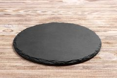 Round slate stand board a wooden background. space for text. Round slate stand board a wooden background. space or text stock photo