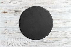 Round slate stand board a wooden background. space for text. Round slate stand board a wooden background. space or text royalty free stock photos