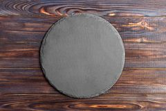 Round slate stand board a wooden background. space for text. Round slate stand board a wooden background. space or text royalty free stock photo