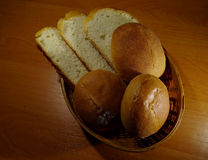 Round slider buns and sloaf slices in wicker breadbasket Royalty Free Stock Photo