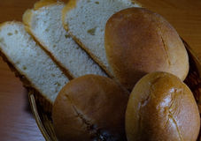 Round slider buns and sloaf slices in wicker breadbasket Stock Photo