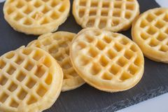 Round small waffles on black slate board with selective focus. On front waffles stock images