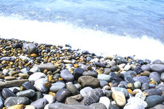 Round smooth stones. On a seashore and wave Royalty Free Stock Images