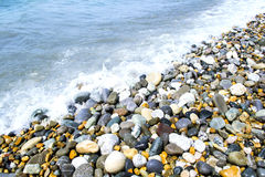 Round smooth stones. On a seashore and wave Stock Photography