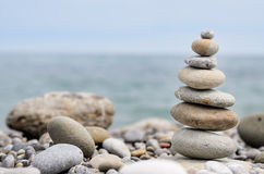Round Smooth Stones Stacked on Rocky Beach Stock Photography