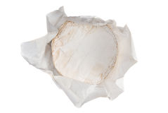 Round soft cheese. In a wrapping paper over white Royalty Free Stock Photography
