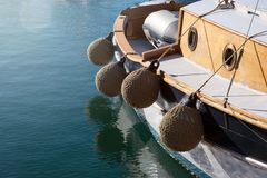 Round soft  mooring fenders, woven from manila rope on a small old ship. stock image