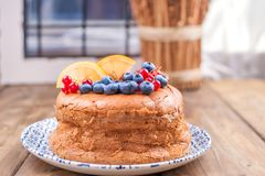 Round sponge cake with currant and blueberry berries on a wooden table. Free space for text. Homemade baking. stock image