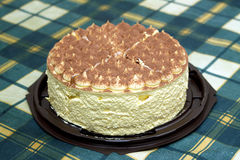 Round sponge cake on green checkered tablecloth on the table Stock Image