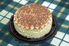 Round sponge cake on green checkered tablecloth on the table Royalty Free Stock Image