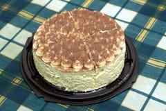 Round sponge cake on green checkered tablecloth on the table. Round sponge cake on green checkered tablecloth on kitchen table. Top view closeup royalty free stock image