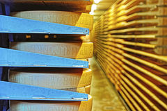 Round stacks of cheese stored on shelves of the Maison du Gruyer Stock Photo