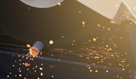 Round steel pipe cutting in factory workshop using metal cut-off grinder machine with heat flame orange sparks royalty free stock photography