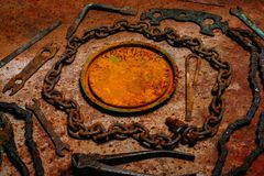 Round steel rusty banner in the center of chain, tools on vintage metal background. Motorcycle tools, equipment and repair. Round steel rusty banner in the stock photos