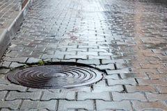 Round steel sewer manhole on wet cobblestone road Stock Image