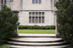 Round Steps at Opening to Grassy Area. Stone steps in front of a historic building with shurbs on each end Stock Image