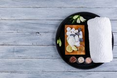 On a round board is pebbles, towel and burning candles for aroma and spa treatments on a wooden surface. On a round stone board there is a layout of various Royalty Free Stock Photos