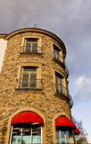 Round Stone Building and Red Awnings. A curved stone wall with iron railings and a red awning Stock Photo