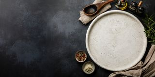 Round stone Dish for cooking Pizza and Spices on dark concrete backdrop Surface copy space stock photo