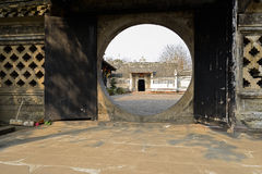 Round stone gate of ancient Chinese building in warm spring Royalty Free Stock Photo