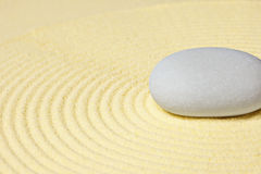 Round stone lying on sand with circular pattern Royalty Free Stock Photography