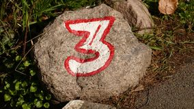 Stone with the number three. Round stone with number three, on the wayside royalty free stock photos
