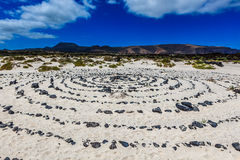A round stone pattern in the sand by a beach Stock Photos