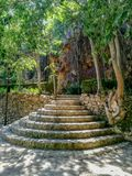 Round stone stairs in natural landscape with stone walls royalty free stock photo