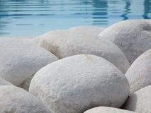 Round stones at the pool. Round white stones standing near the pool, as an abstract pattern Royalty Free Stock Images