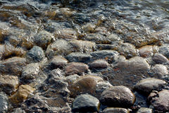 Round stones and water. Round stones covered with water, waves Royalty Free Stock Photos