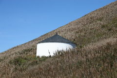Round Storehouse on Hillside. Unusual circular-shaped storage building on a steep hillside covered with vegetation...picture taken in Oregon, U.S.A. on the west Royalty Free Stock Image