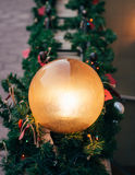 Round street lamp glowing among Christmas decorations Stock Photo