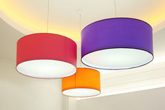 Round stylish lampshades hang from ceiling. Purple, red and orange round stylish lampshades hang from ceiling royalty free stock image