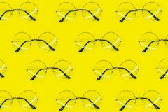Round sunglasses pattern on yellow background. Minimal summer pattern. Flat lay royalty free stock images
