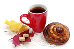 Round sweet bun and cup of tea Royalty Free Stock Images