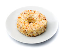 Round sweet dessert cheese with nuts and pineapple on a white pl Royalty Free Stock Image