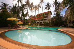 Round swimming pool, sun loungers next to the garden and buildings. Swimming pool at the hotel at the resort. The buildings, sun chairs, nice view. A place to Royalty Free Stock Image